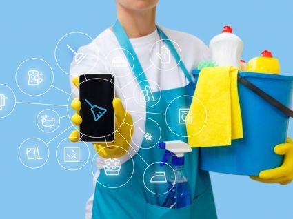 pessoa a segurar balde com produtos de limpeza e telefone