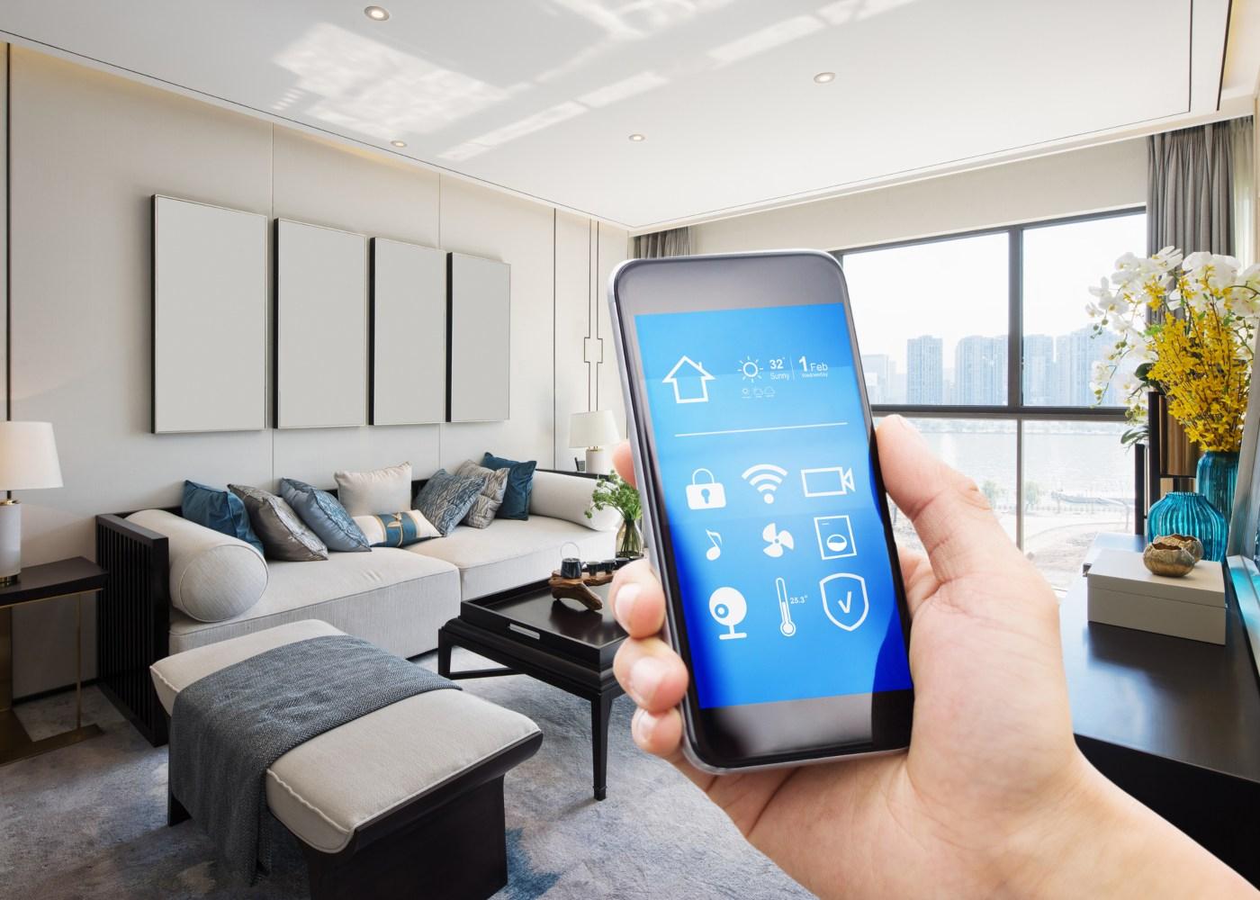 pessoa na sala a segurar o telefone com apps de casa ativas