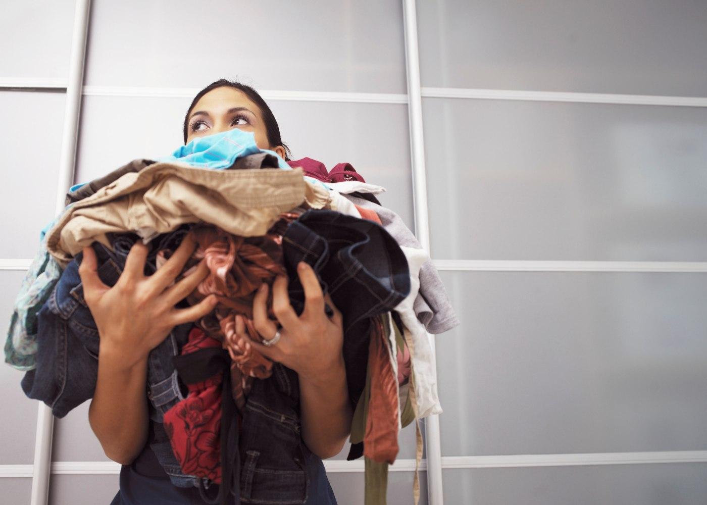 mulher cheia de roupa a ver como organizar tarefas domésticas