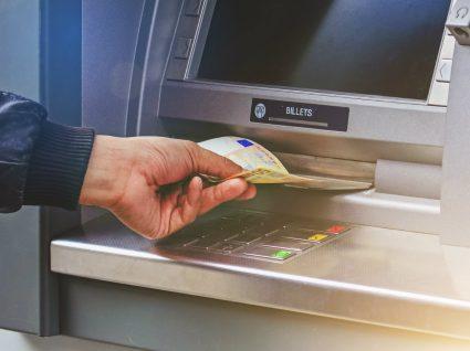 Homem levanta diheiro num caixa multibanco