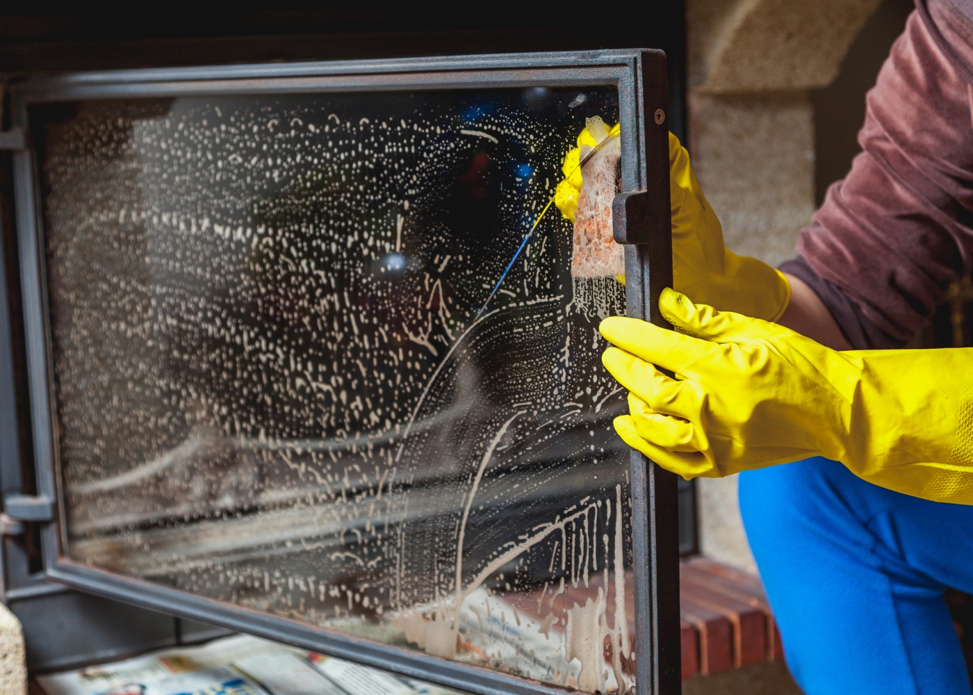 pessoa a lavar vidro da porta da lareira