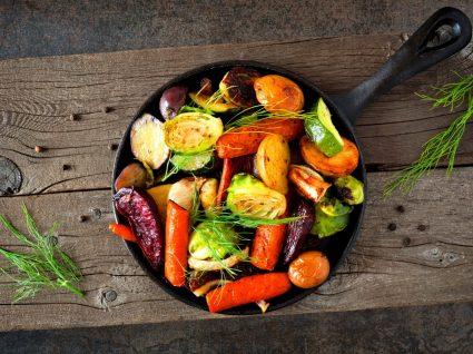 frigideira com legumes em cima de tábua de madeira