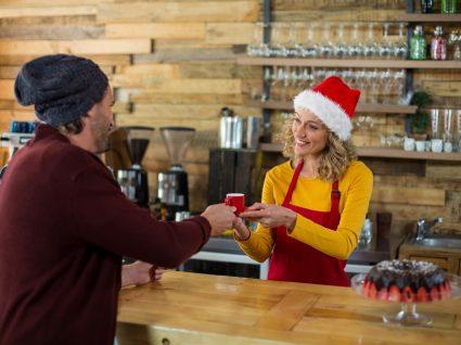barista com chapéu de natal a atender cliente