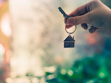 pessoa a segurar chave com porta-chaves com uma casinha