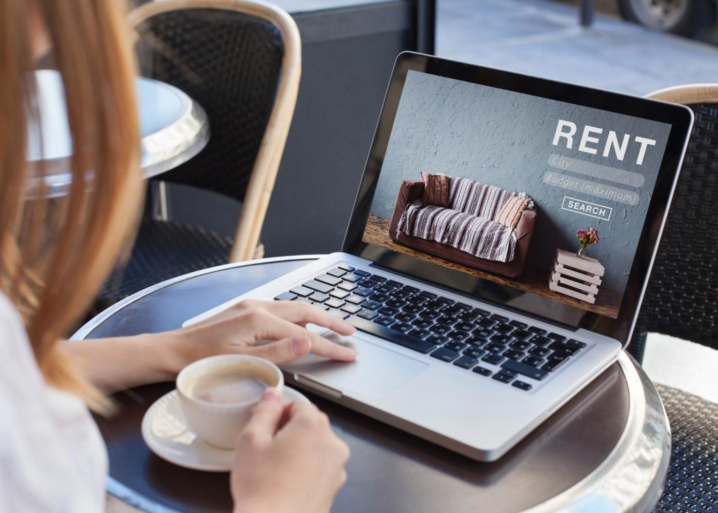 mulher no café à procura de casas para arrendar no computador