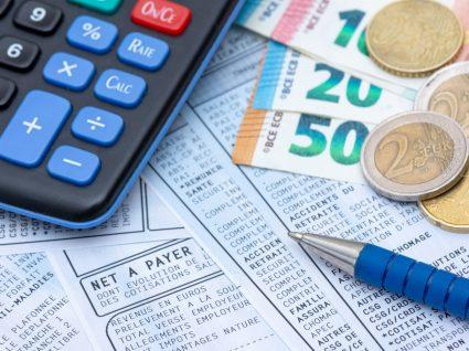 canela, calculadora e dinheiro numa mesa para saber o salário bruto