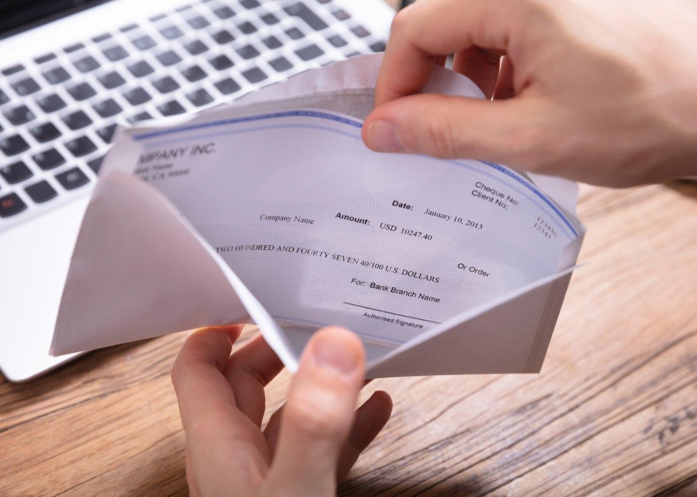pessoa a abrir envelope com o ordenado