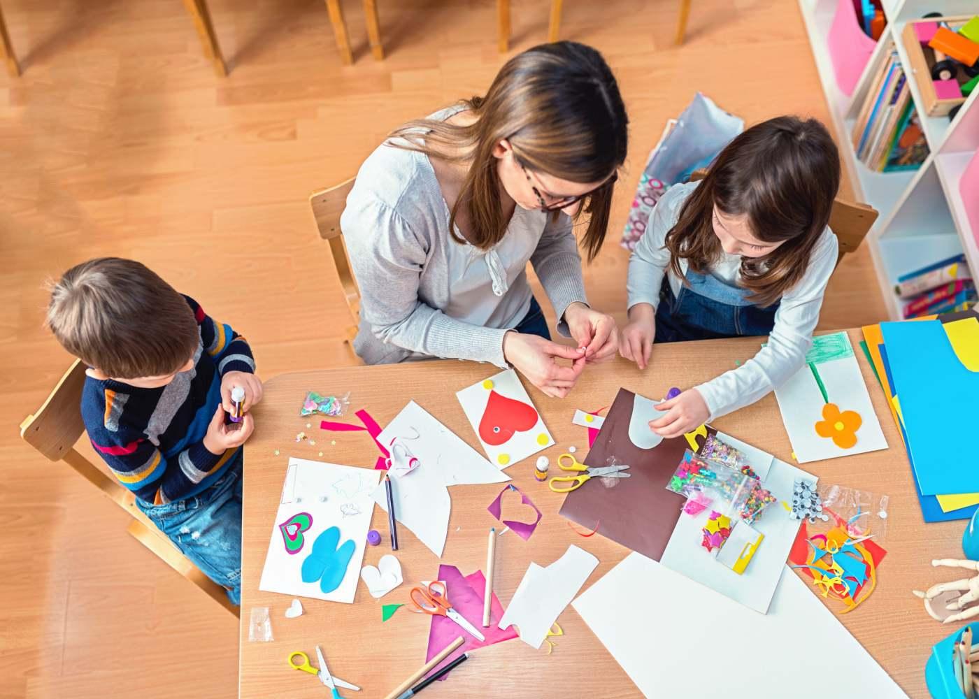 mulher a fazer trabalhos manuais com crianças