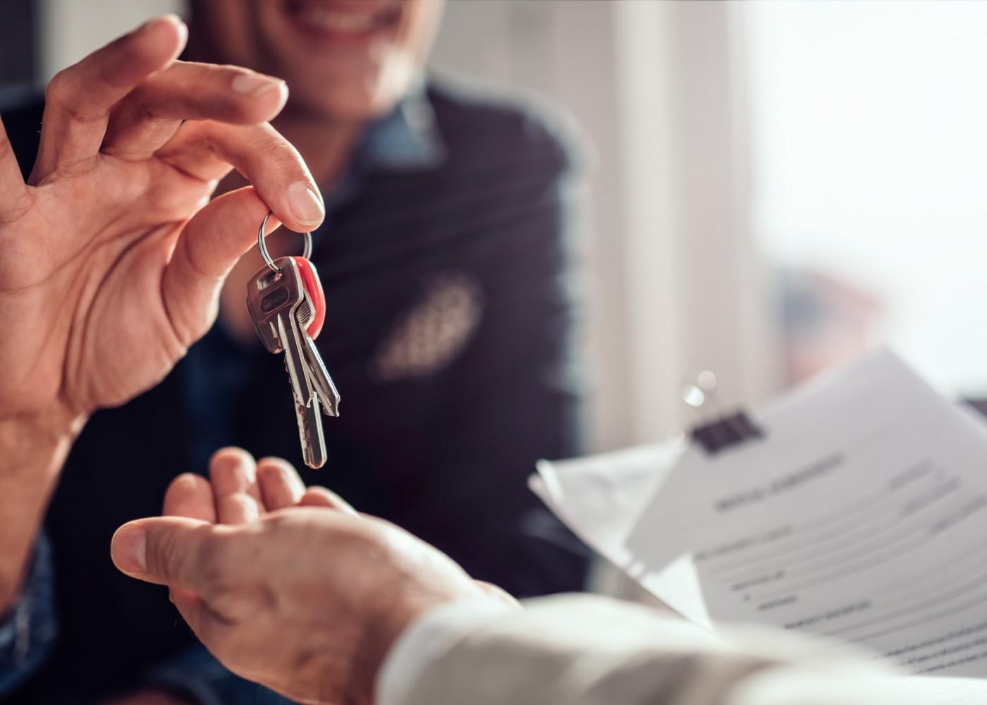 pessoa a entregar chave de casa a outra