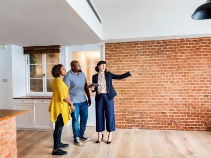 casal a visitar uma casa com a consultora imobiliária