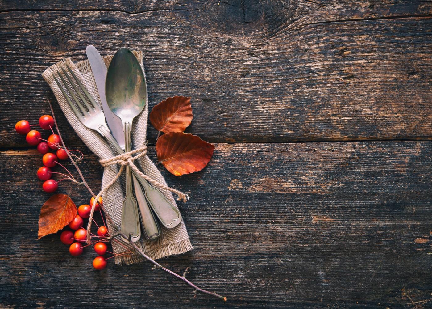 mesa de madeira com arranjo de talheres, guardanapo e azevinho