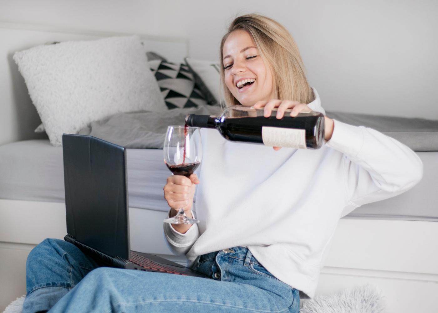 rapariga no computador a beber vinho