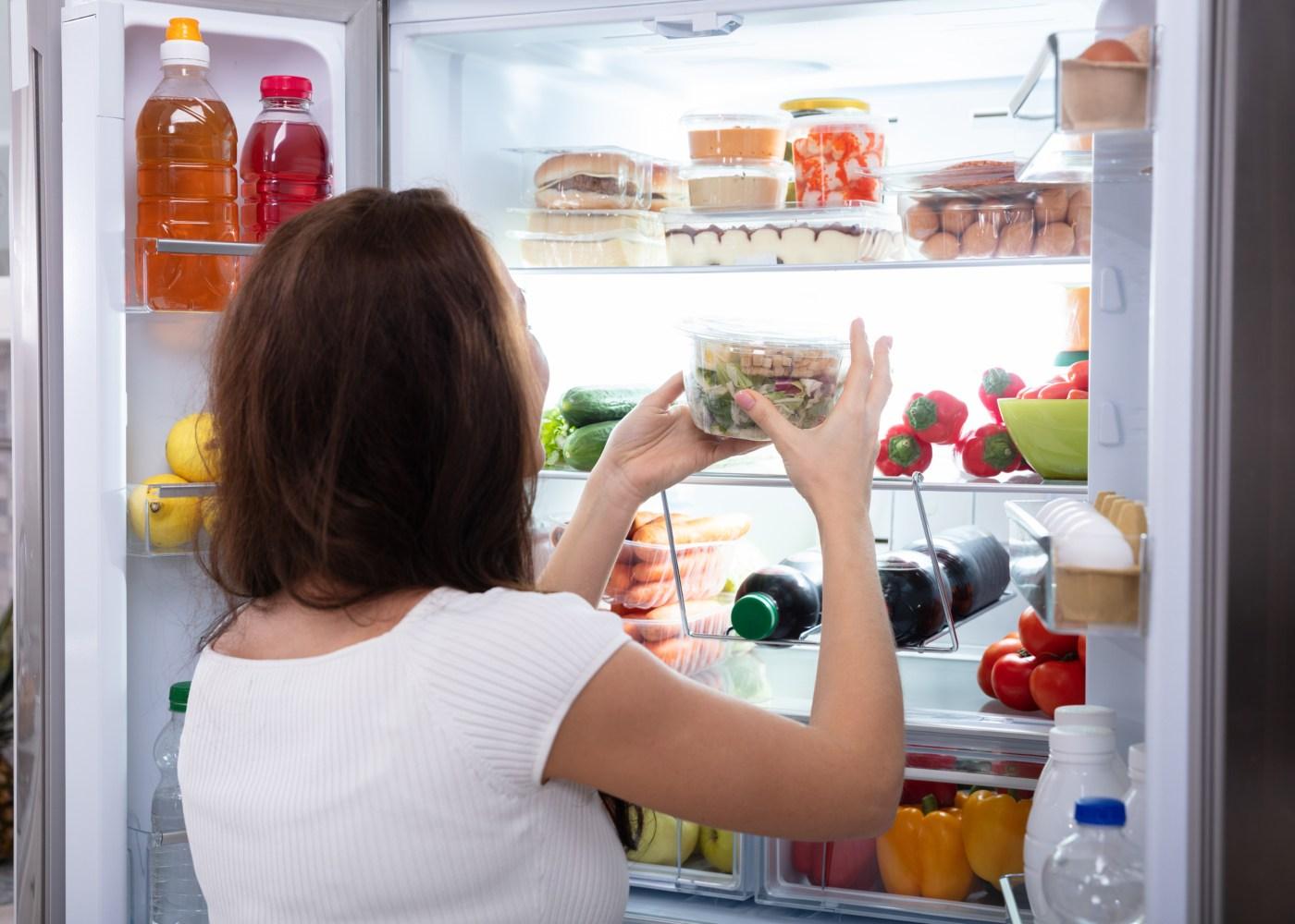 mulher a guardar embalagem no frigorífico
