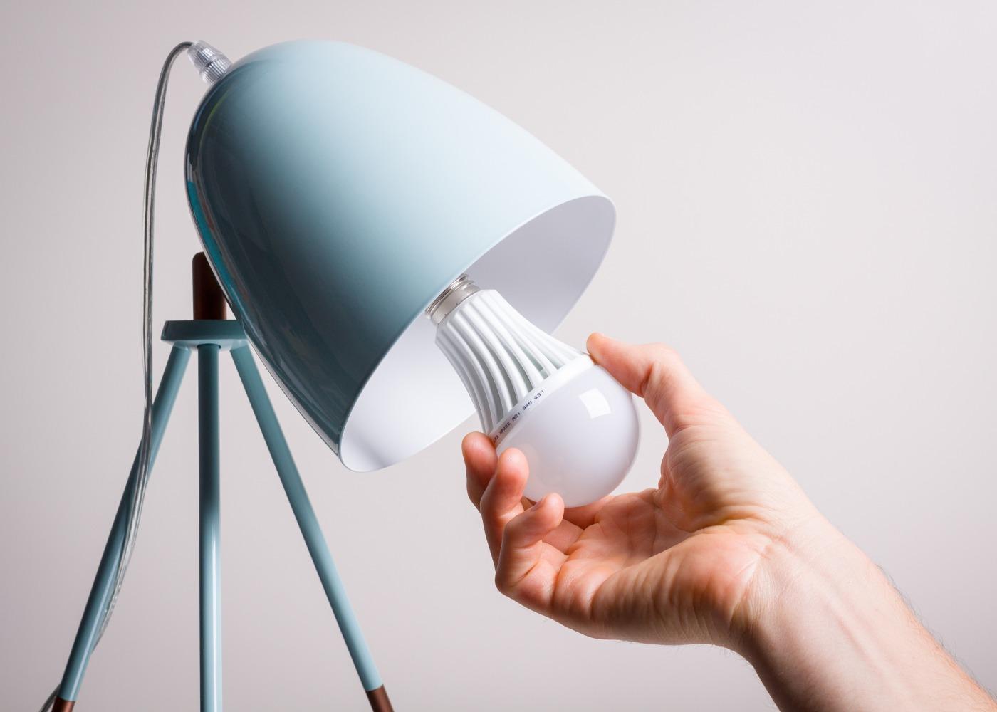 mão a colocar lâmpada led num candeeiro