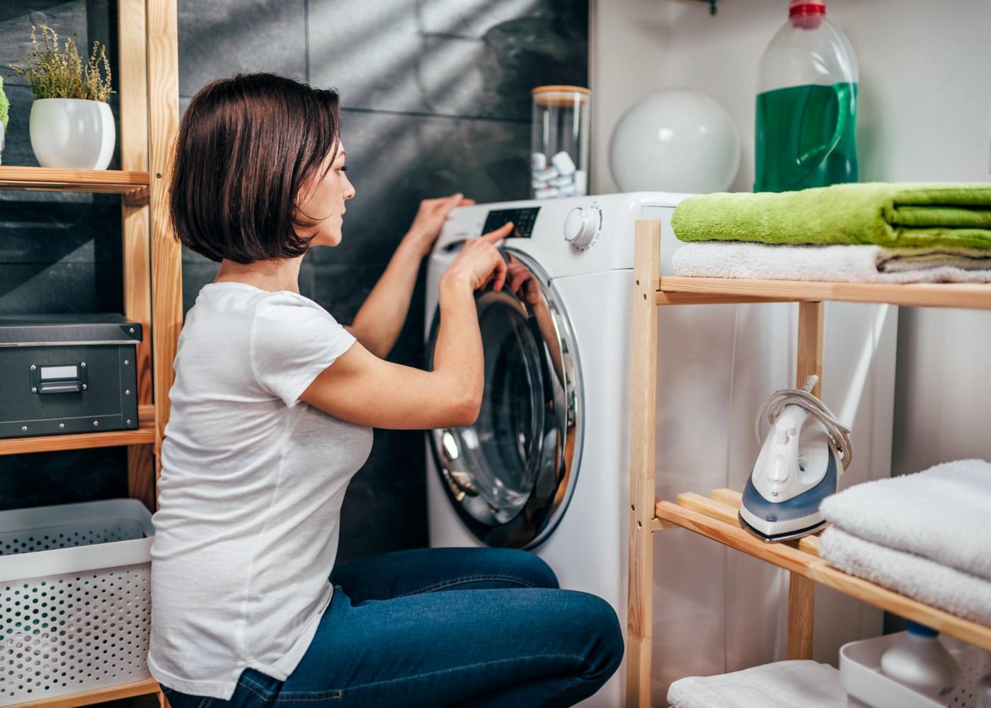 mulher a por a máquina da roupa a lavar