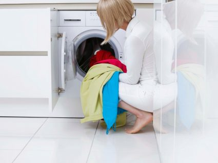 mulher a limpar a máquina de lavar a roupa