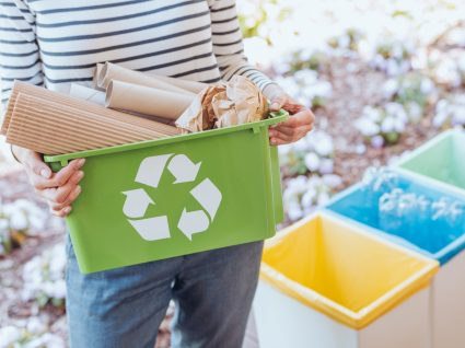 mulher a segurar caixote de reciclagem com cartão