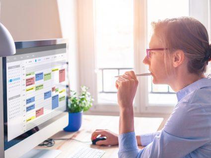 mulher a olhar concentrada para a sua agenda no computador para analisar produtividade
