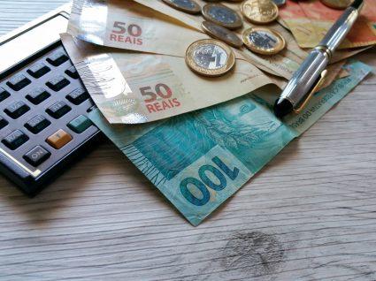 dinheiro, calculadora e caneta em cima de mesa