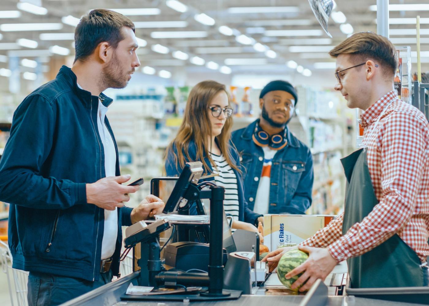 empregado no supermercado a passar compras dos clientes na caixa