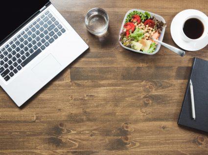 secretária com computador, salada e café