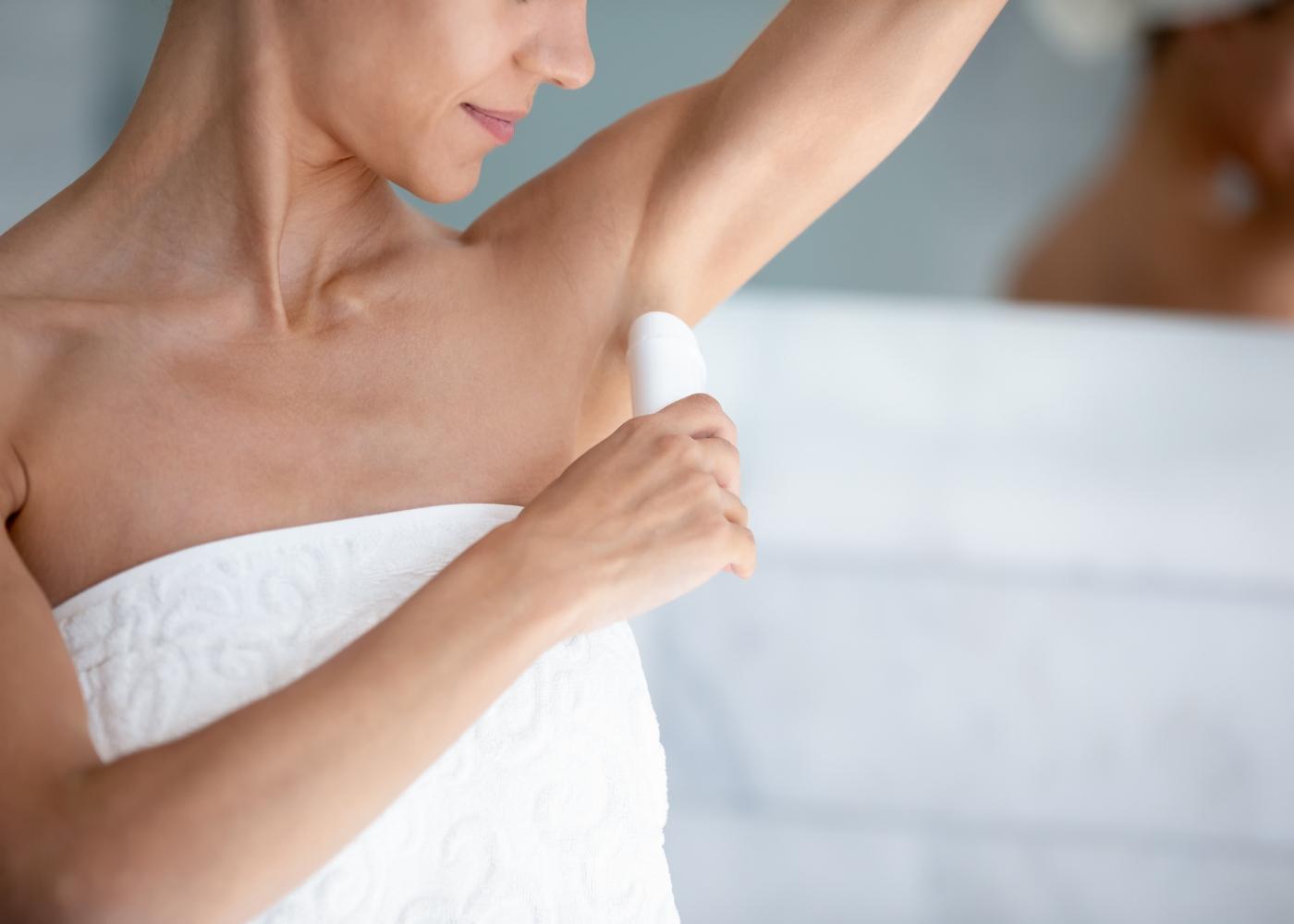 mulher a colocar desodorizante