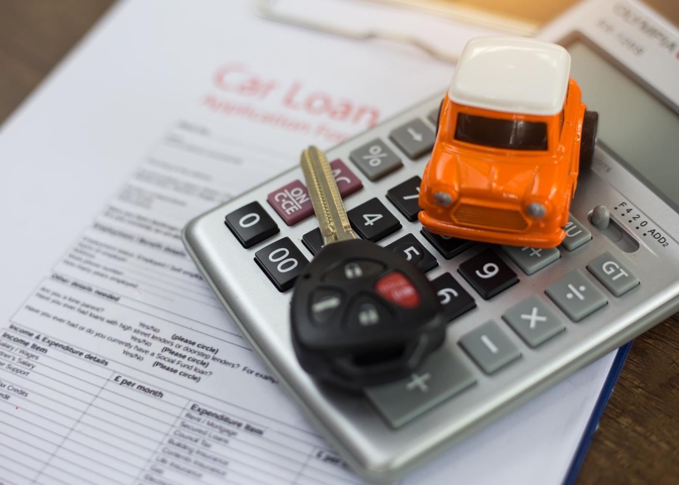 calculadora, carro e chave em cima de papéis