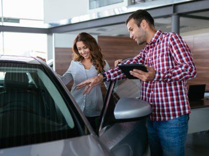 mulher a ver veículo antes de comprar carro usado a um particular
