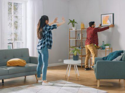 casal a pendurar quadro na sala