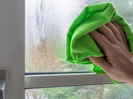 pessoa a limpar humidade da janela