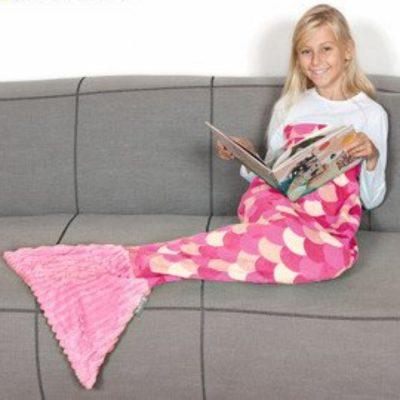 criança a ler com manta de sereia cor de rosa