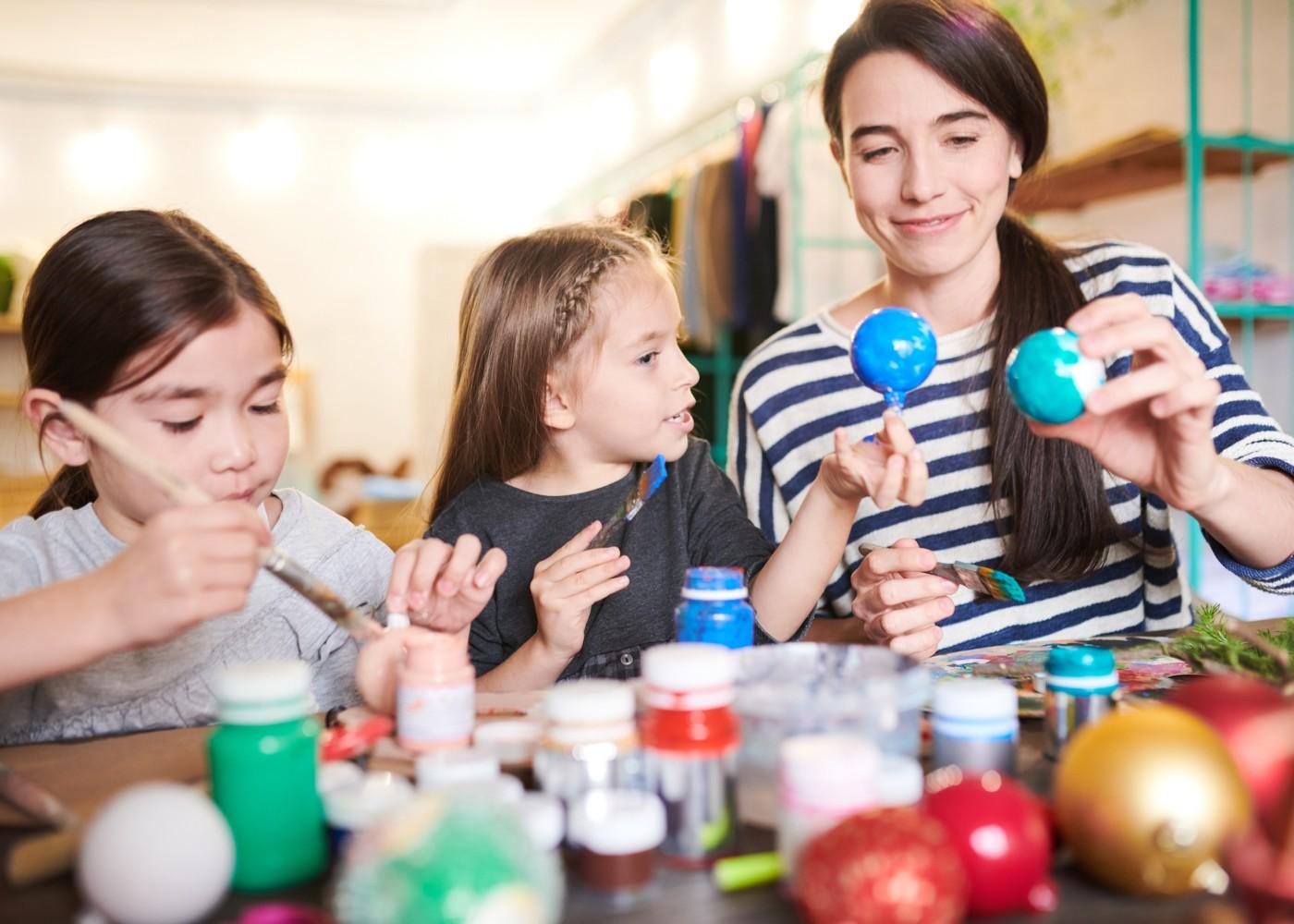 jovem mulher a fazer atividades manuais com crianças