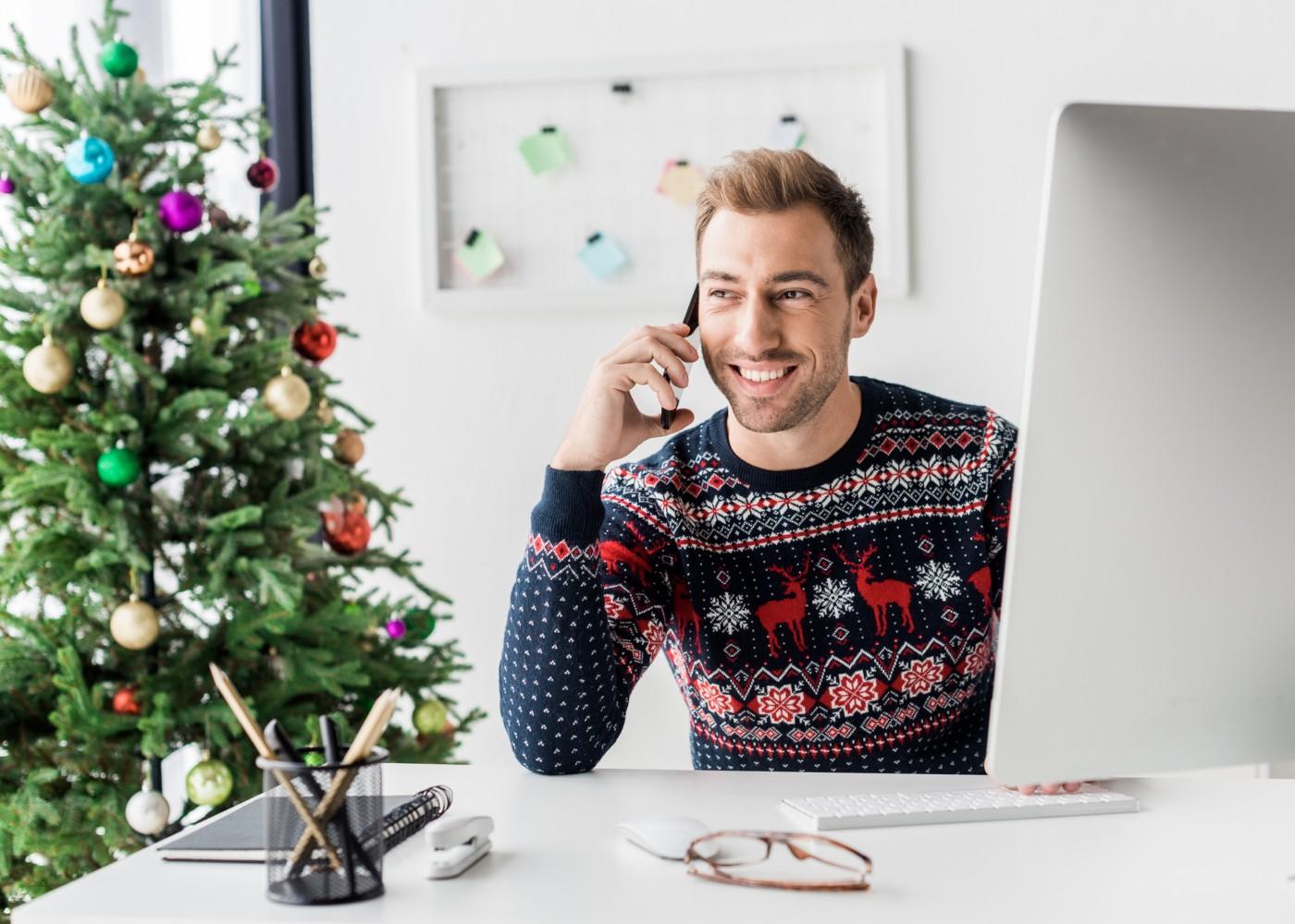 jovem com camisola de natal a trabalhar num escritório