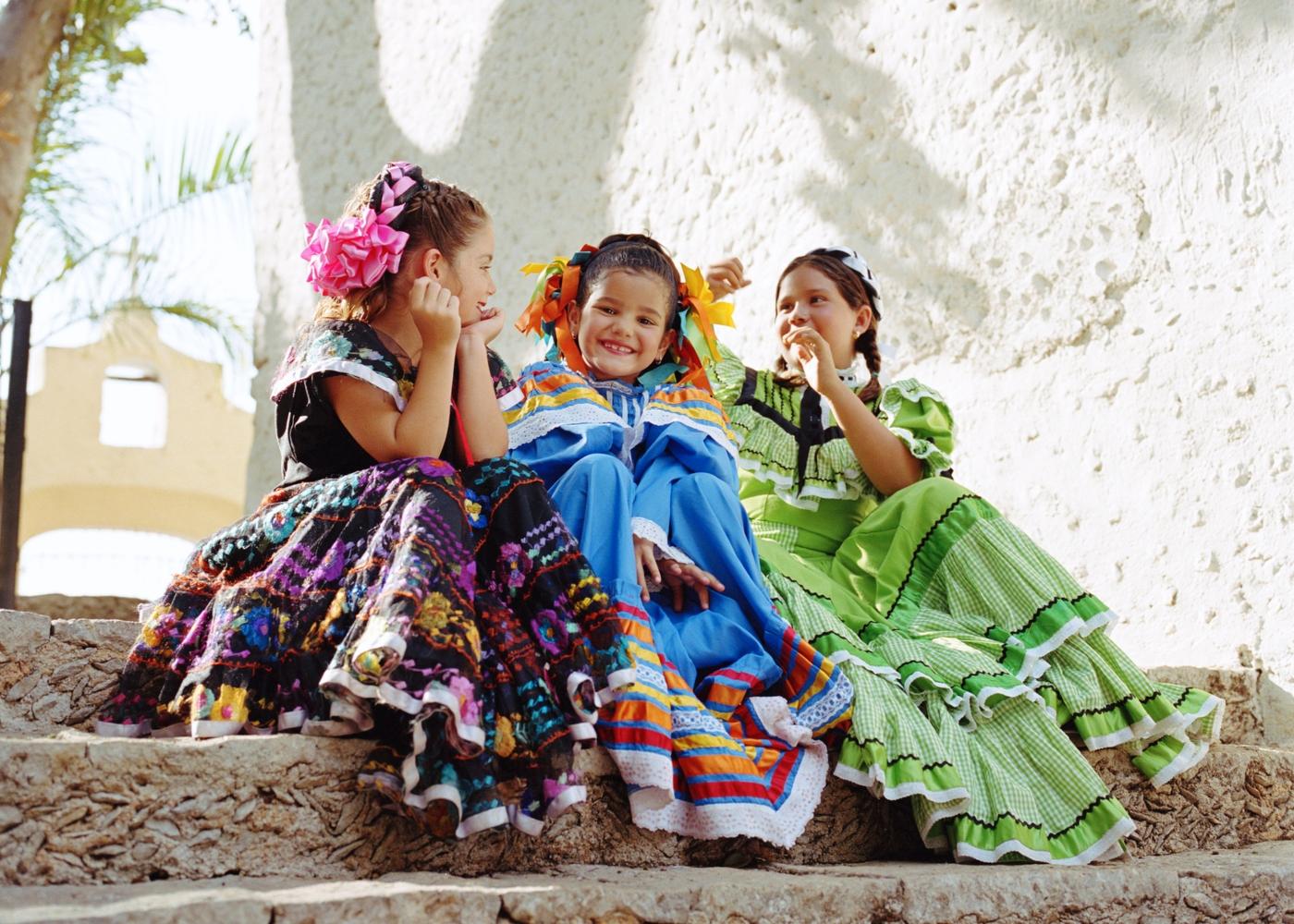 três crianças sentadas vestidas para o carnaval