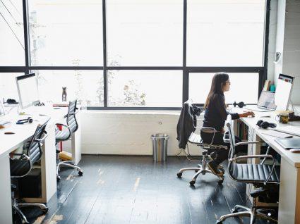 condições de trabalho em portugal: mulher a trabalhar em escritório open space