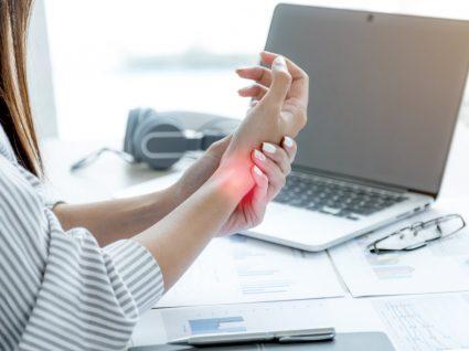 mulher ao computador queixosa de doença profissional tendinite
