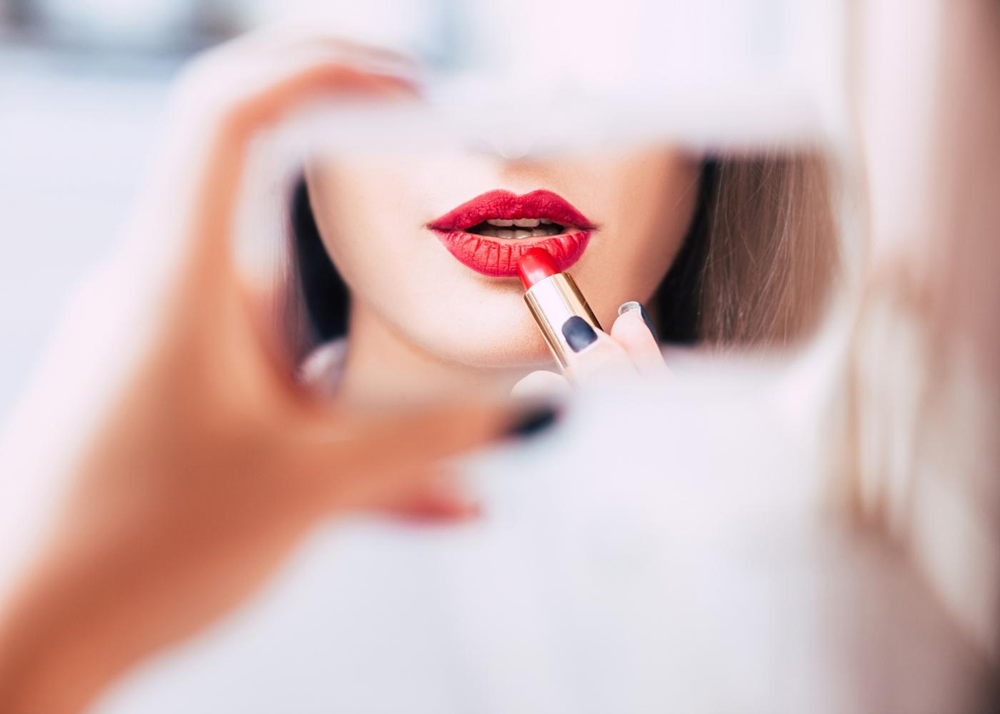 jovem a colocar batom com espelho