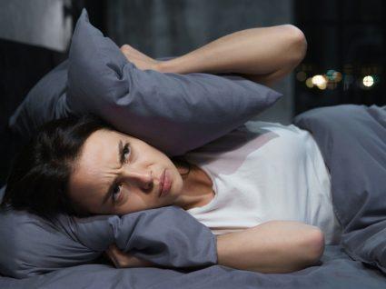 mulher deitada a tapar os ouvidos com a almofada por causa do ruído