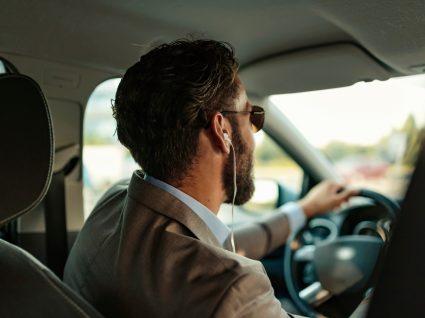 homem a conduzir com auriculares