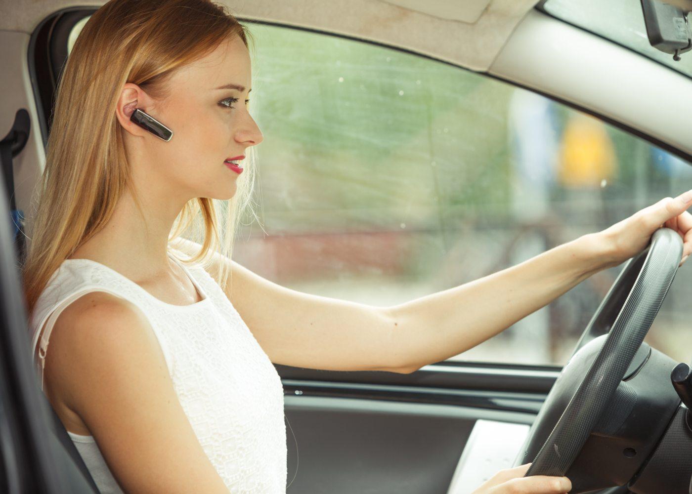 mulher a conduzir com auricular