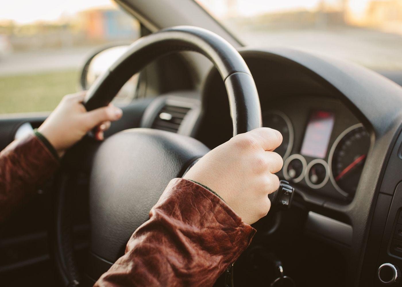 pessoa com as mãos no volante