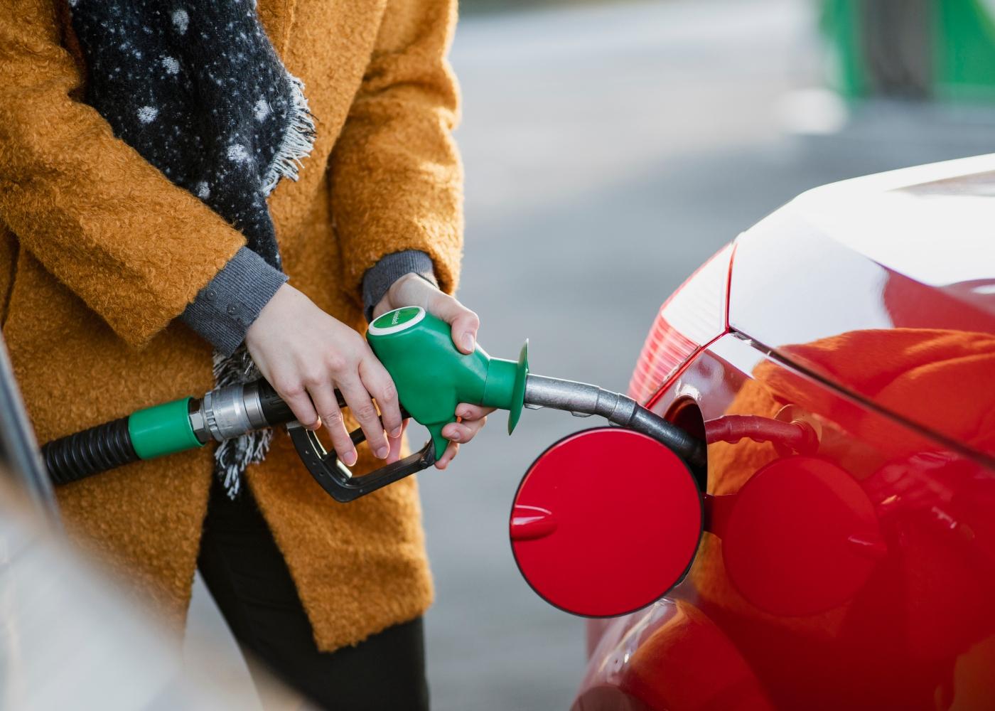 mulher a por combustível no carro