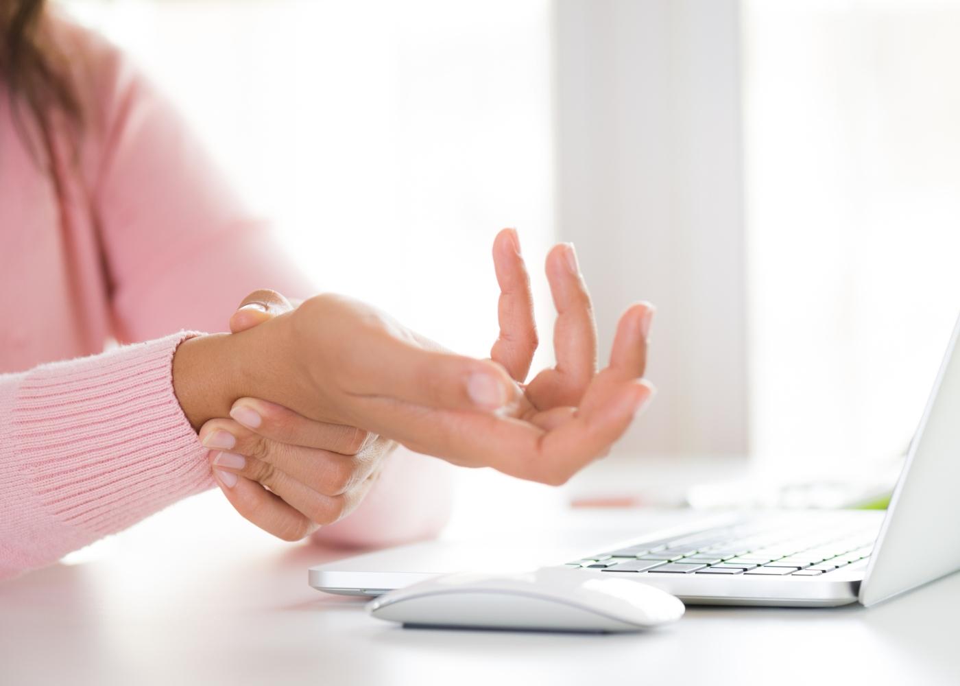 pessoa ao computador a queixar-se do pulso