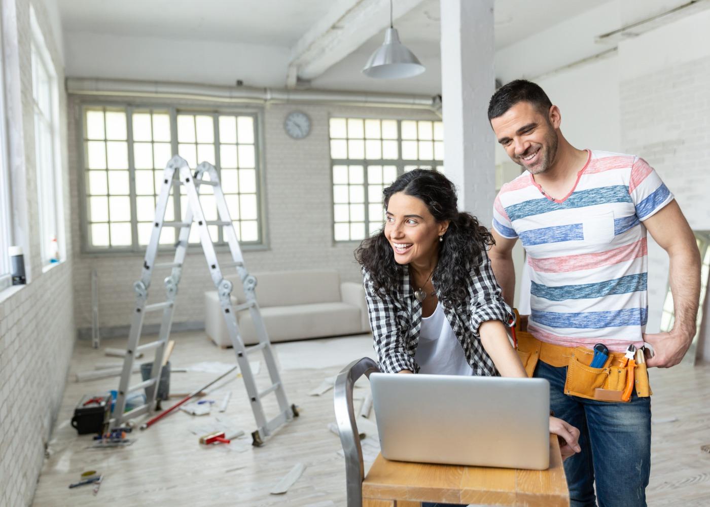 casal numa casa a ser remodelada a ver planos no computador