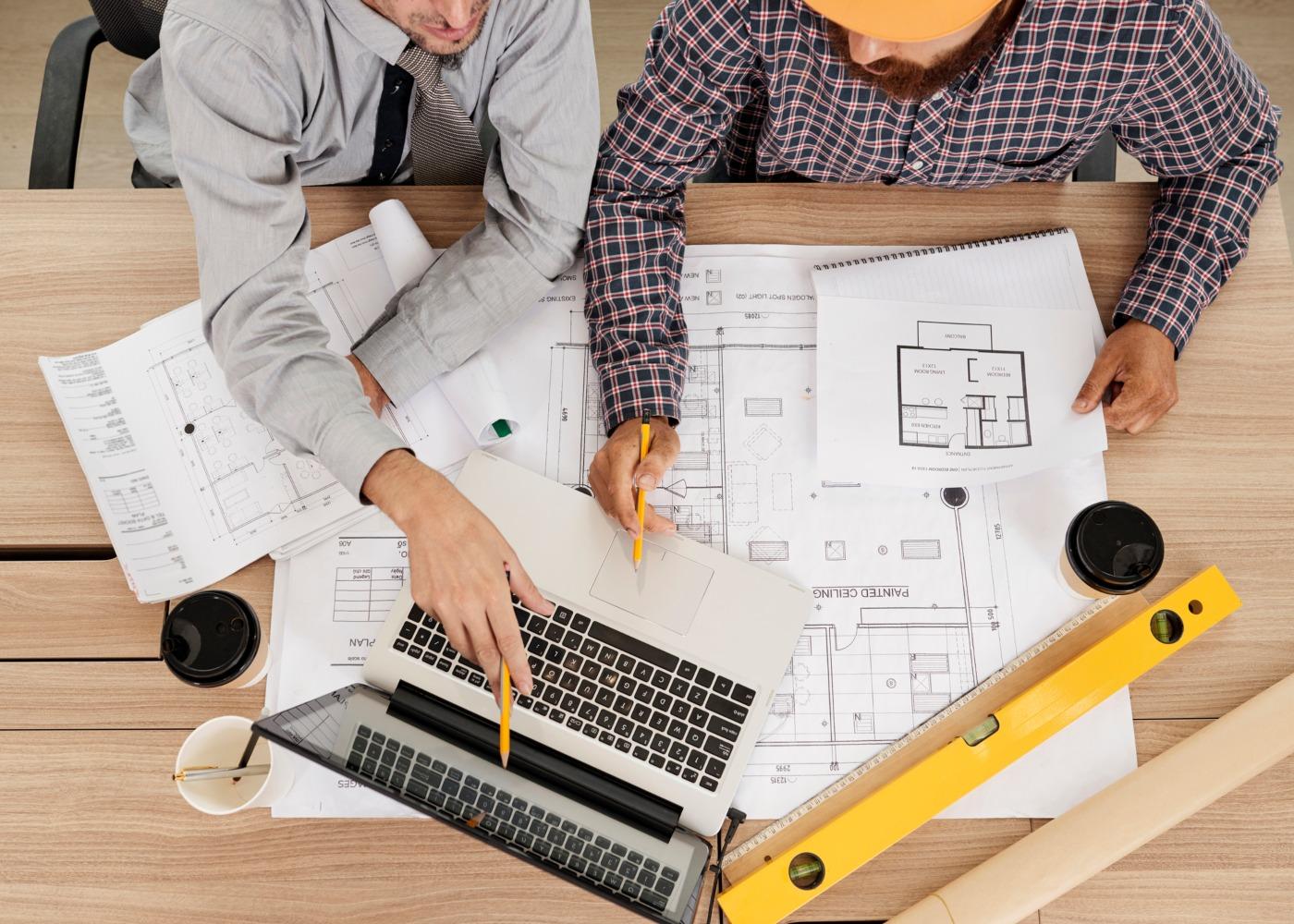 duas pessoas a ver um projeto de remodelação de uma casa no computador e nas plantas em papel