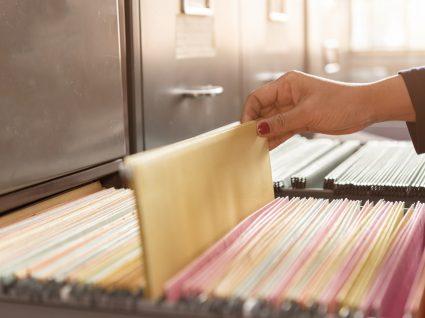 pessoa a tirar ficheiro de armario arquivador