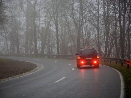 carro a circular com nevoeiro e tempo de inverno
