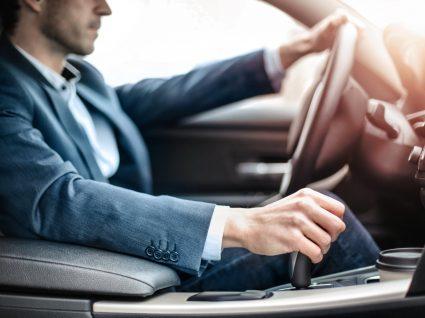 homem a conduzir com mão na caixa, um dos principais vícios ao volante