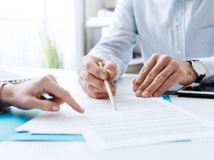 duas pessoas a analisar documentos do subsídio social de desemprego inicial
