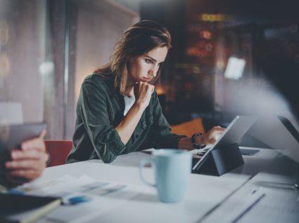 mulher com ar pensativo a procurar informações no tablet